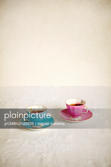 Tea Cups with Letter on Tablecloth - p1248m2125836 by miguel sobreira