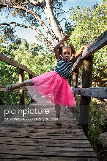 Little girl in pink tulle skirt balancing on one leg - p1640m2246853 by Holly & John