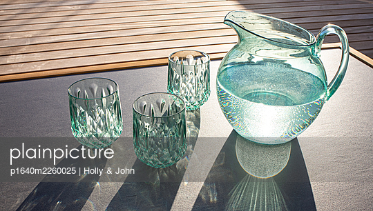 Glass carafe and glasses in the sunshine - p1640m2260025 by Holly & John