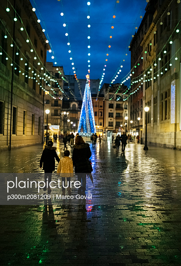 Spain, Gijon, back view of mother and two children walking at pedestrian area in the evening at Christmas time - p300m2081209 by Marco Govel