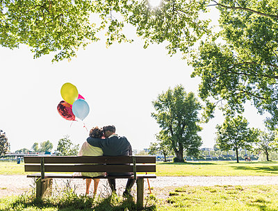 Happy senior couple with balloons sitting on bench in a park - p300m1460390 by Uwe Umstätter