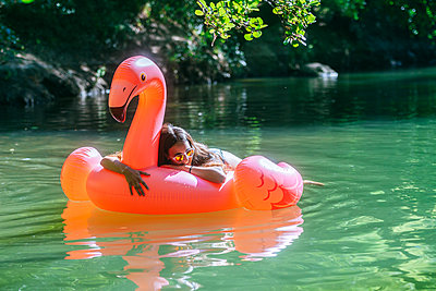 Woman floating on water on an inflatable flamingo - p300m2042127 by Kiko Jimenez