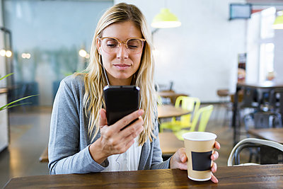 Young woman texting with her mobile phone while drinking coffee in the coffee shop - p300m2114587 by Josep Suria