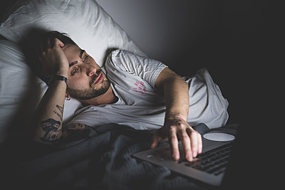 Bearded young man lying in bed at night, looking at laptop.  - p429m2202294 by Eugenio Marongiu