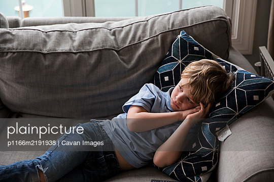 Sad Blonde Boy Watches TV While Laying on Couch - p1166m2191938 by Cavan Images