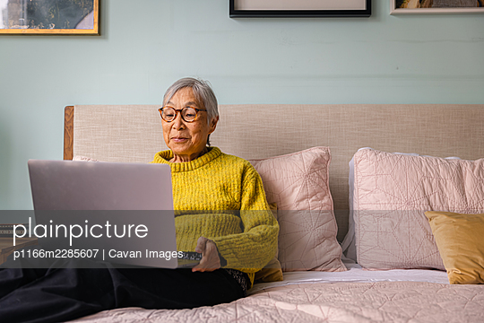 Senior asian woman using laptop while sitting in bedroom at home - p1166m2285607 by Cavan Images