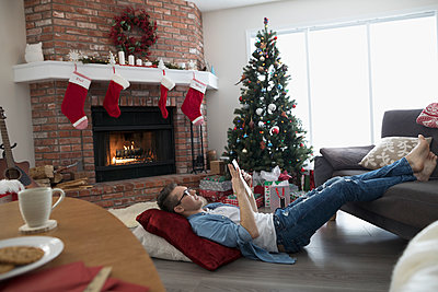 Young man relaxing, using digital tablet on floor in Christmas living room - p1192m1512233 by Hero Images