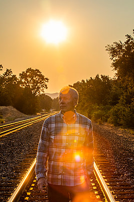 Senior man walking on railroad tracks at sunset - p1427m2085069 by Steve Smith