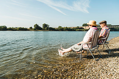 Germany, Ludwigshafen, senior couple sitting on folding chairs at riverside splashing with feet in water - p300m1069063f by Uwe Umstätter