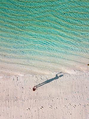 Indonesia, Bali, Melasti, Aerial view of Karma Kandara beach, woman standing on the beach - p300m2042594 by Konstantin Trubavin
