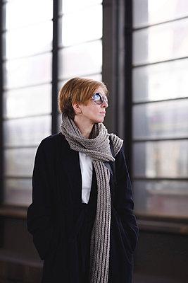 Mature woman with sunglasses wearing black coat and long wool scarf waiting at platform - p300m2139770 by Ekaterina Yakunina