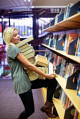 Female student carrying pile of books in a library - p300m975527f by zerocreatives