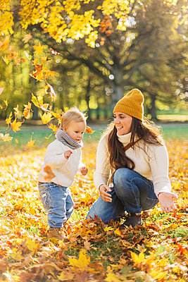 Mother and son playing in autumn leaves in Sweden - p352m1536610 by Calle Artmark