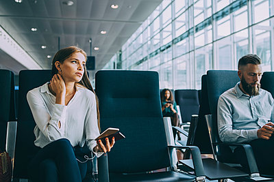 Thoughtful young businesswoman looking away while sitting by colleague at waiting area in airport - p426m2074782 by Maskot
