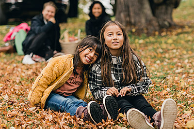 Portrait of smiling sisters sitting on autumn leaves during picnic with parents - p426m2194952 by Maskot