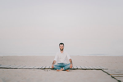 Caucasian man sitting on boardwalk at beach - p555m1504009 by Kateryna Soroka