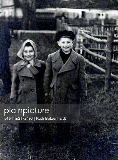 Siblings in coats in the countryside - p1541m2172493 by Ruth Botzenhardt