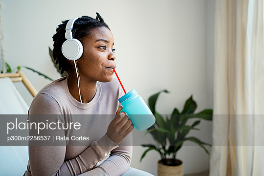 Young woman looking away while drinking coffee at home - p300m2256537 by Rafa Cortés