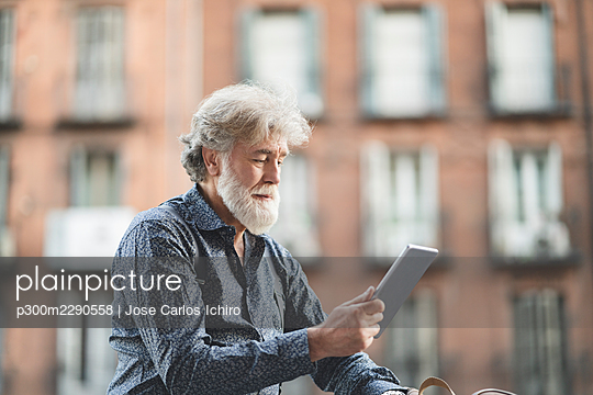 Mature man with white hair using digital tablet in city - p300m2290558 by Jose Carlos Ichiro
