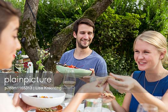 Freunde beim Essen im Garten - p788m1165313 von Lisa Krechting