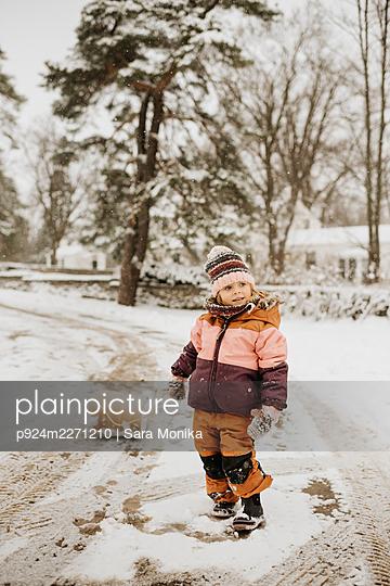 Canada, Ontario, Girl (2-3) standing on snowy road - p924m2271210 by Sara Monika