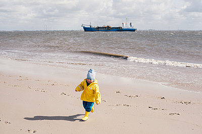 Little boy wearing oilskin jacket on beach - p1046m1467531 by Moritz Küstner
