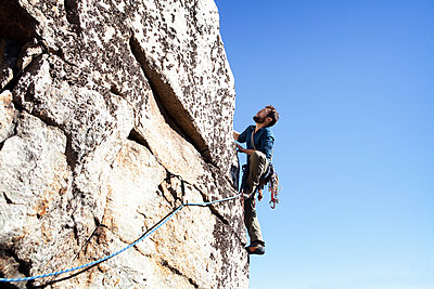 Low angle view of man rock climbing against clear sky - p1166m1231470 by Cavan Images