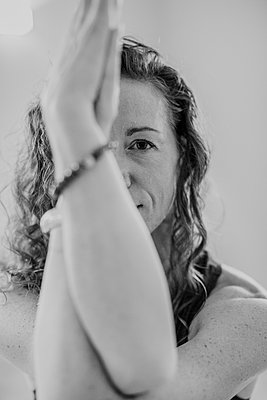 black and white image of woman's face while practicing yoga in a studi - p1166m2153747 by Cavan Images