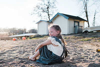 portrait of a young girl sitting on the sand at sunset smiling - p1166m2189853 by Cavan Images