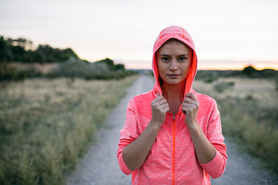 Beautiful woman with hooded jacket standing at country road - p300m2273517 by Andrés Benitez