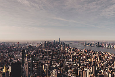 Buildings in Manhattan by river against sky seen from Empire State Building, New York City, USA - p301m1498550 by Norman Posselt