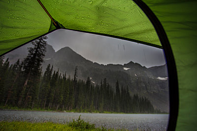 A storm as seen from inside a small tent while backpacking in the Crazy Mountains in Montana. Heavy rain over a lake at dusk. - p343m1218108 by Jess McGlothlin Media