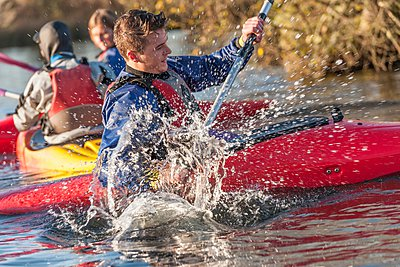 Young man kayaking - p429m1021608f by Colin Hawkins