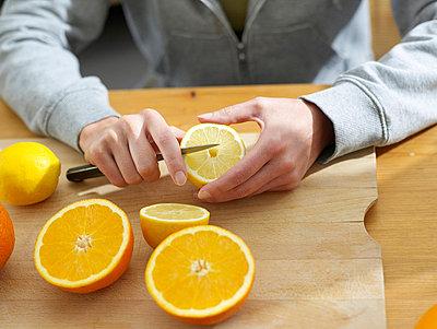 Frau schneidet Zitrone  - p6430255f von senior images RF