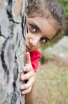 Little girl peeking from a behind a tree  - p794m1119724 by Mohamad Itani