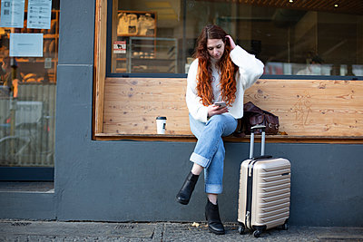 Young woman with trolley bag and smartphone - p975m2223797 by Hayden Verry