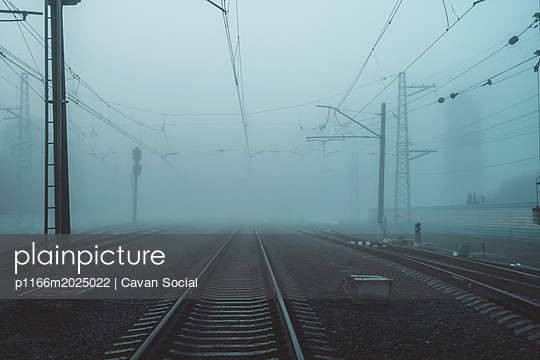Railroad tracks by electricity pylons in city during foggy weather