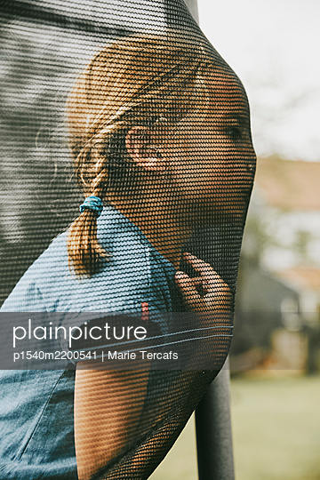 little girl with pigtails playing outside - p1540m2200541 by Marie Tercafs