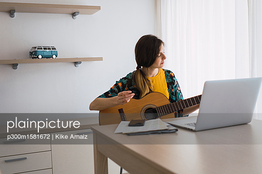 Young woman sitting at table at home with laptop playing guitar - p300m1581672 von Kike Arnaiz