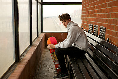 Teenage Boy in Shelter holding Skateboard. Direct to Camera - p1304m1136840 by MY MY