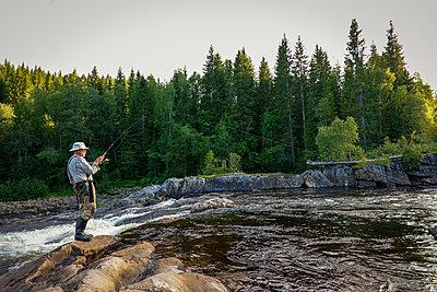 Elderly man fishing in river - p1418m2007539 by Jan Håkan Dahlström