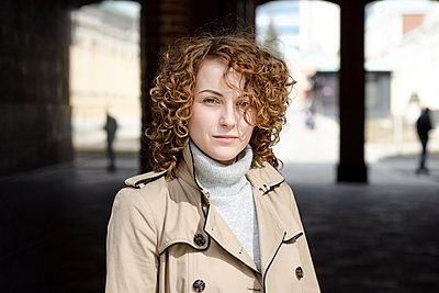 Portrait of woman with curly hair wearing beige trenchcoat and turtleneck pullover - p300m2102932 by Ekaterina Yakunina