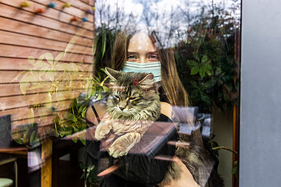 Portrait of girl with surgical mask and cat behind window pane - p300m2181082 by Sandra Roesch