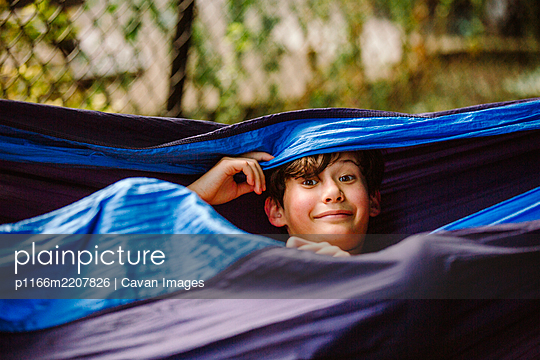 A smiling child with a goofy expression peers out from a hammock - p1166m2207826 by Cavan Images