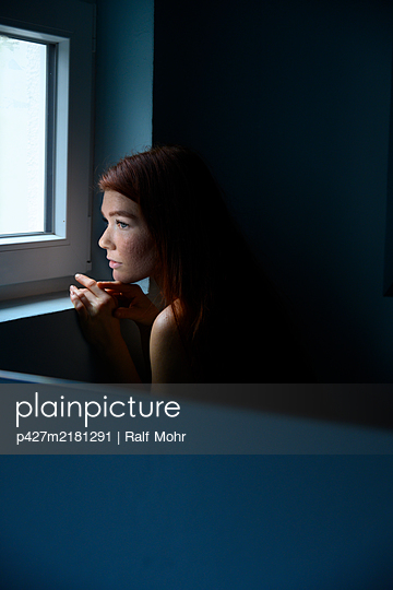 Anxious woman with red hair looking out of window - p427m2181291 by Ralf Mohr