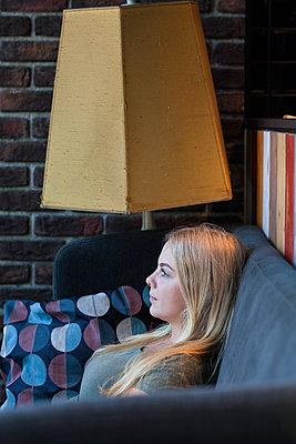 Frau sitzt nachdenklich auf Sofa - p045m2008425 von Jasmin Sander
