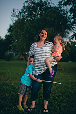 Portrait of smiling mother with cute children standing on grassy field against trees in park during sunset - p1166m2066429 by Cavan Images