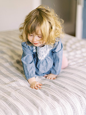 Little toddler girl taking a break from jumping on her parent's bed. - p1166m2152350 by Cavan Images