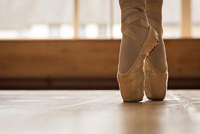 Ballerina dancing on wooden floor in dance studio - p1315m2017672 by Wavebreak