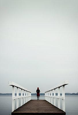 Frau auf einem Holzsteg am See - p1574m2147976 von manuela deigert